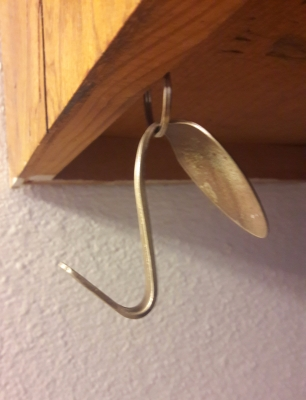 Slide thin end of spoon through ring (which is hanging from an eye hook
